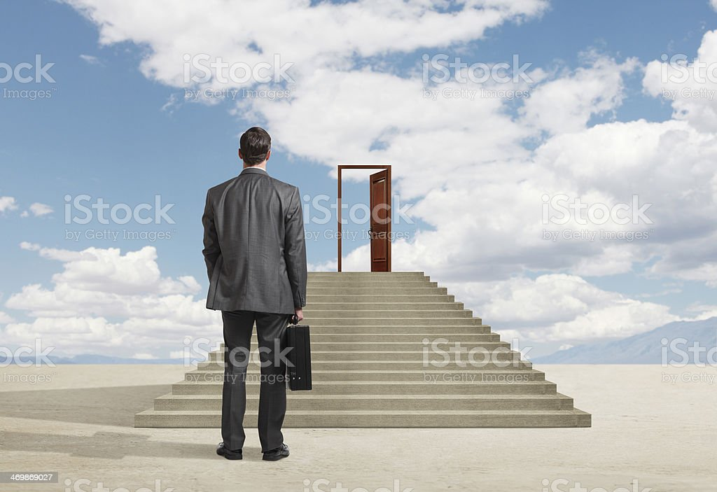 Businessman looking at opportunity created by an open door stock photo