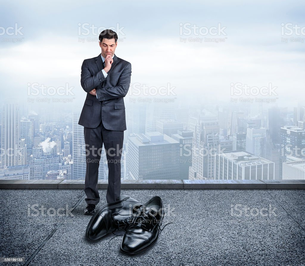 Businessman Looking At Pair Of Big Shoes To Fill stock photo