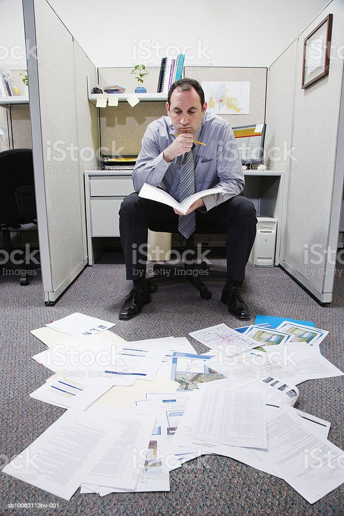 Businessman looking at papers lying on floor royalty free stockfoto