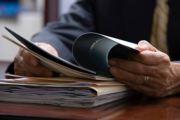 Businessman looking at paperwork Businessman looking at paperwork ring binder stock pictures, royalty-free photos & images