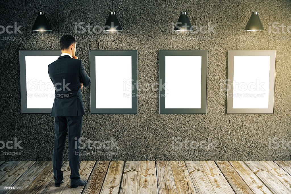 Businessman looking at picture frames stock photo