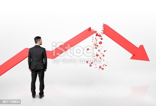 istock Businessman looking at red broken arrow of falling graph isolated 601148804
