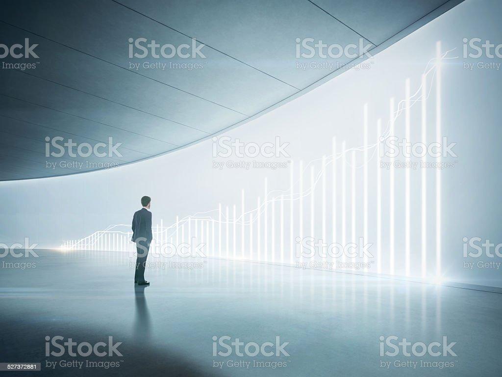 Hombre de negocios mirando a la brillante cuadro en la pared - Foto de stock de Adulto libre de derechos