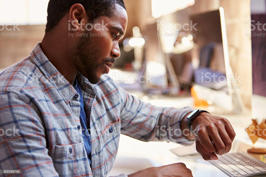 Businessman Looking At Smart Watch In Design Office stock photo