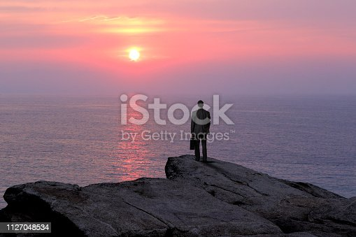A businessman stands with his back to the camera while holding his briefcase as he stands on top of a rocky cliff and looks out as the sun is about to set into the ocean.