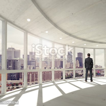 Businessman on black suite and long hair looking at the big from his office in a skyscraper.