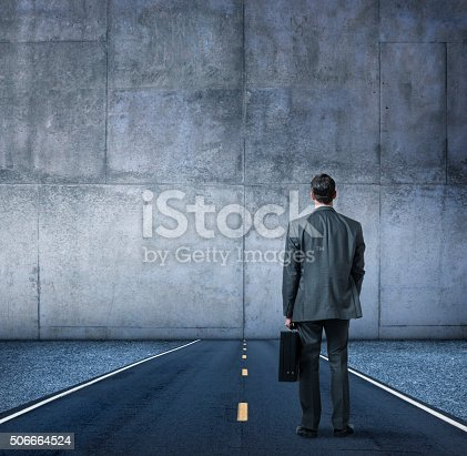 A businessman, with his back to the camera while holding a briefcase, stands in the middle of a road that runs directly into a large concrete wall.