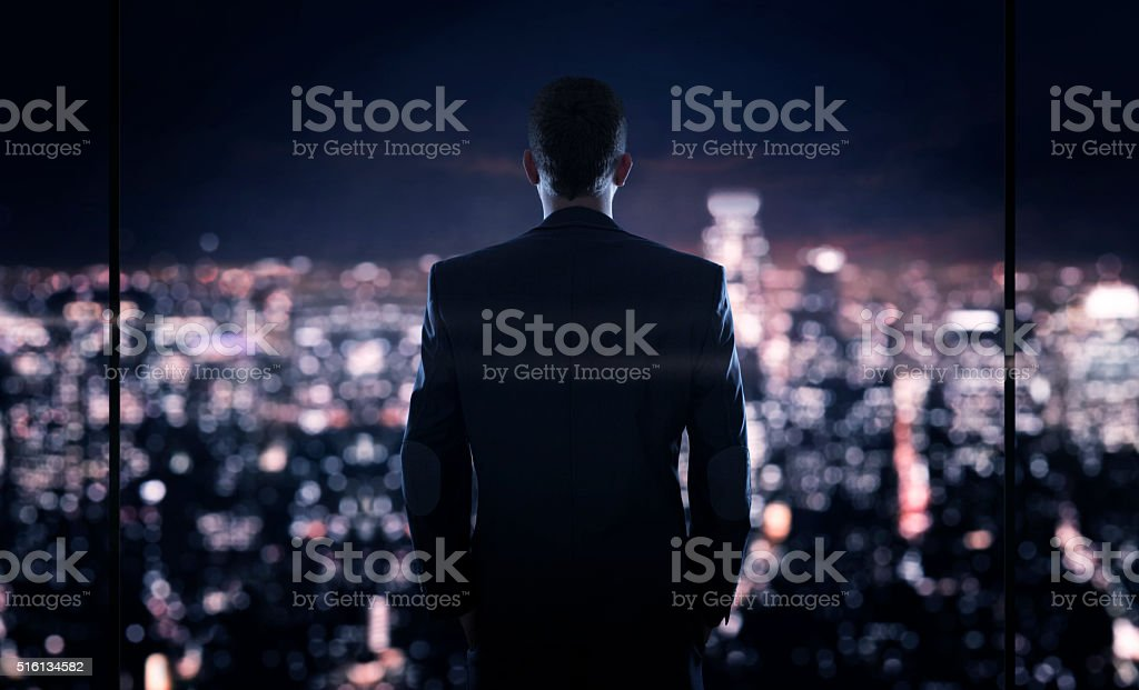 Businessman looking at the the city at night stock photo