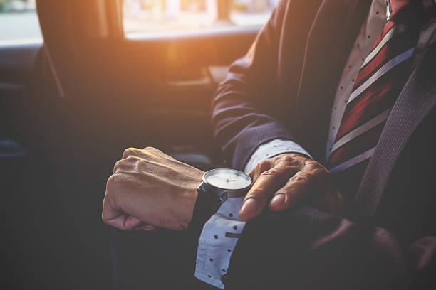 Businessman looking at the time on his wrist watch in car. Business concept. stock photo