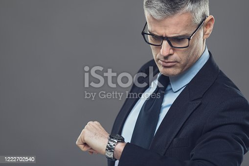 Businessman looking at the time on his wristwatch with copy space