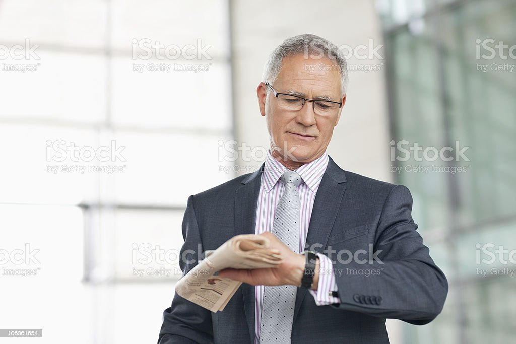 Businessman looking at watch in airport royalty-free stock photo