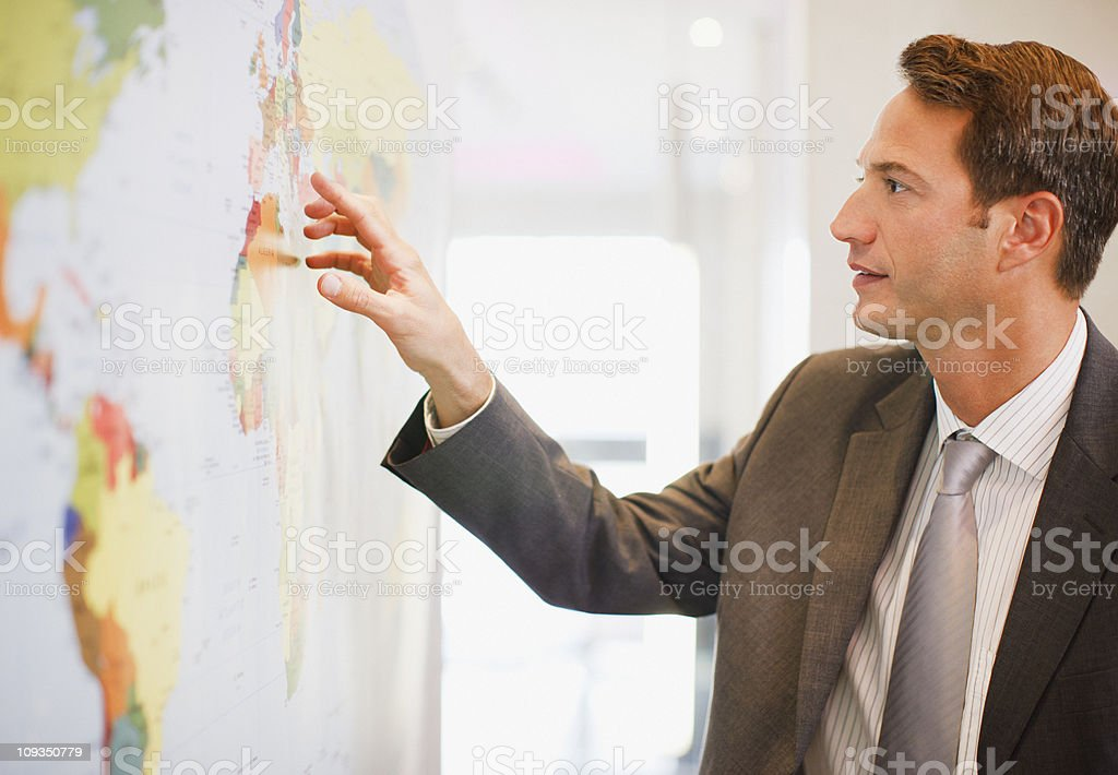 Businessman looking at world map stock photo