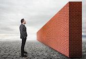 Businessman looking brick wall.