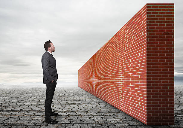 Businessman looking brick wall stock photo