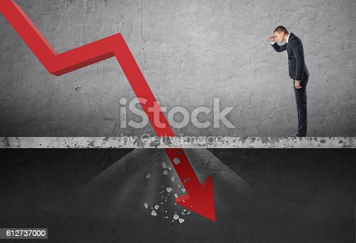 istock Businessman looking down at the falling red arrow destroying a 612737000