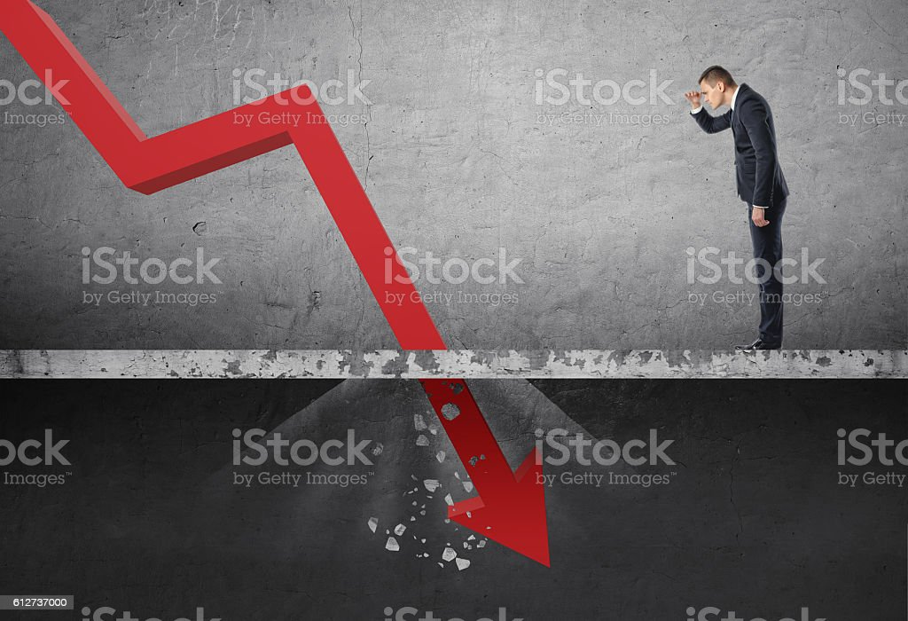 Businessman looking down at the falling red arrow destroying a stock photo