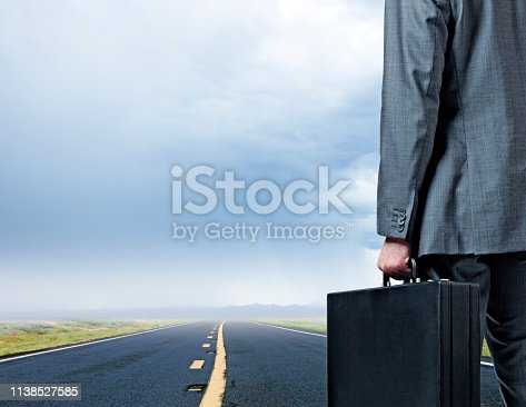 A close up of a businessman carrying a briefcase as he stands in front in front of a rural road that disappears on the horizon as he is dwarfed by the beautiful clouds and sky above him.  The scene evokes an emptiness and loneliness that is magnified by the stark and barren nature of the surroundings.