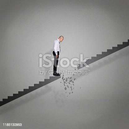 1048837520 istock photo Businessman Looking Down on Broken Stairs 1185130953