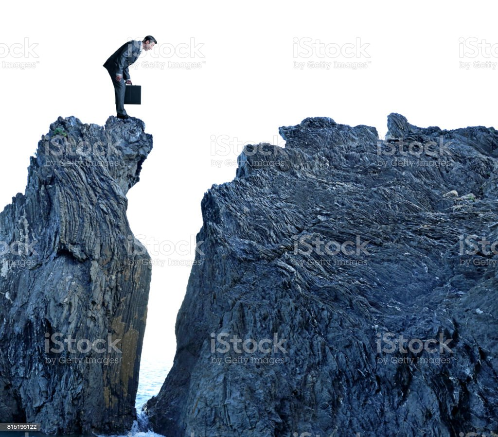 Businessman Looking Down On Top Of Rocky Cliff Above Ocean stock photo