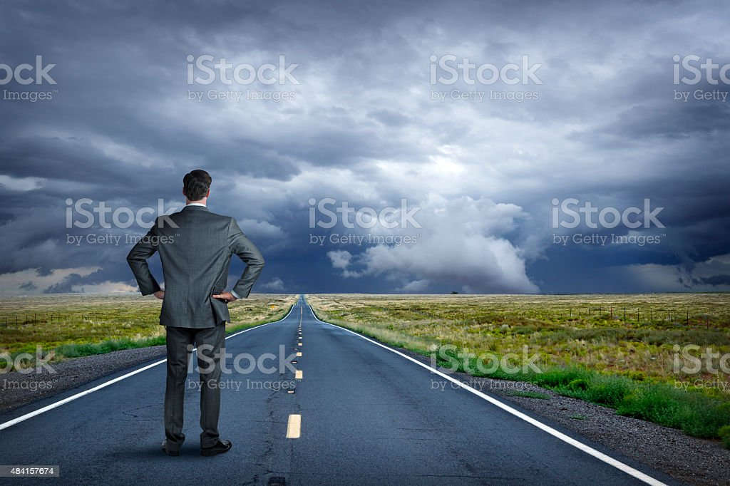 Businessman Looking Down Road At Approaching Storm stock photo
