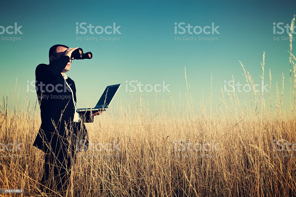Businessman looking field for investment. stock photo