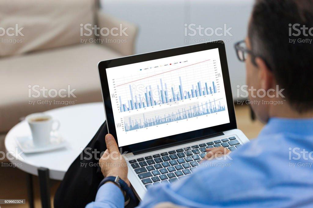 Geschäftsmann sucht Finanz-Charts auf laptop – Foto