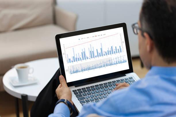 businessman looking financial charts on laptop - diagramma a colonne foto e immagini stock