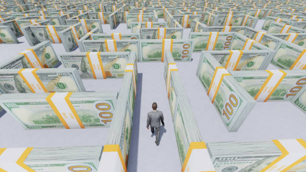 Businessman looking for a way out of the Money Maze made of one hundred usd banknotes. stock photo