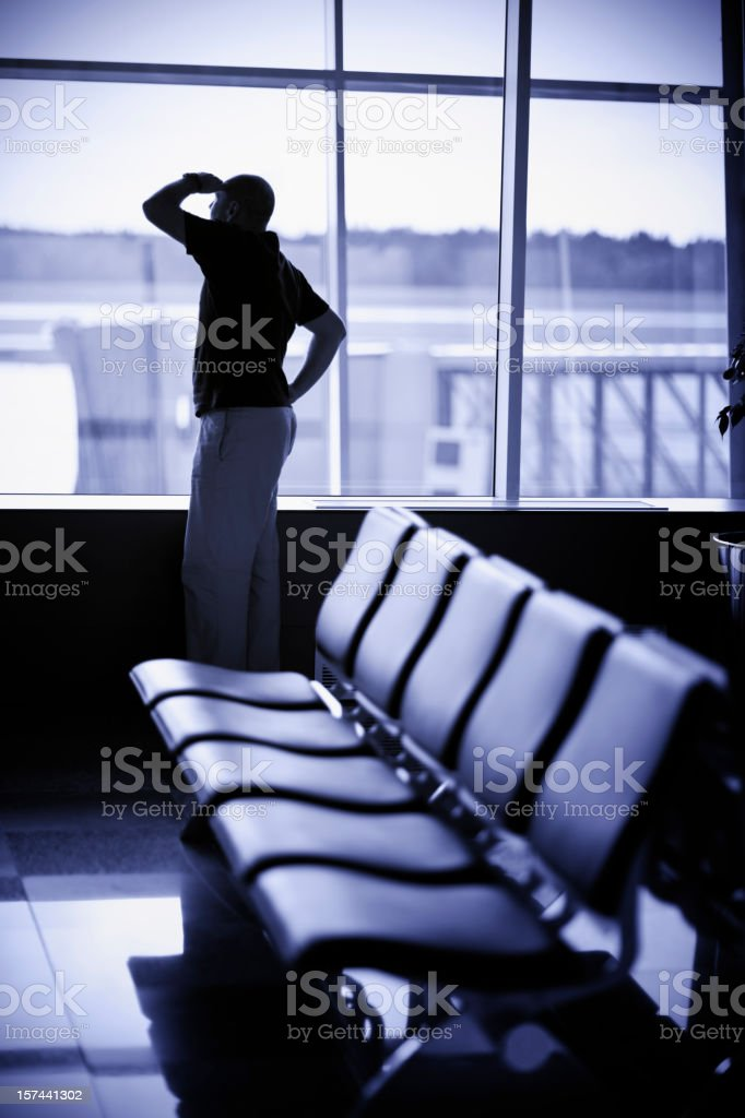 Businessman looking for delayed plane royalty-free stock photo