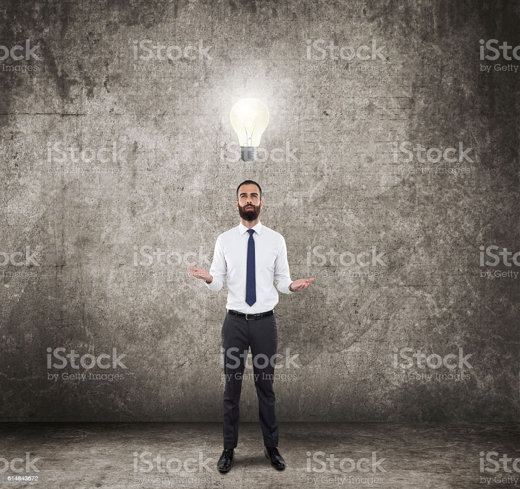Businessman looking glowing light bulb stock photo