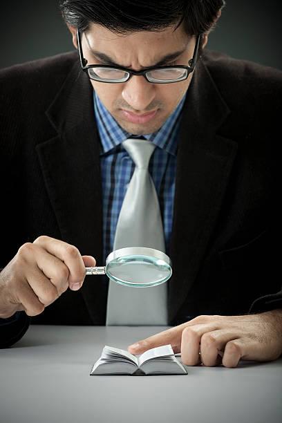 Geschäftsmann in einer Miniatur-Buch mit Lupe – Foto