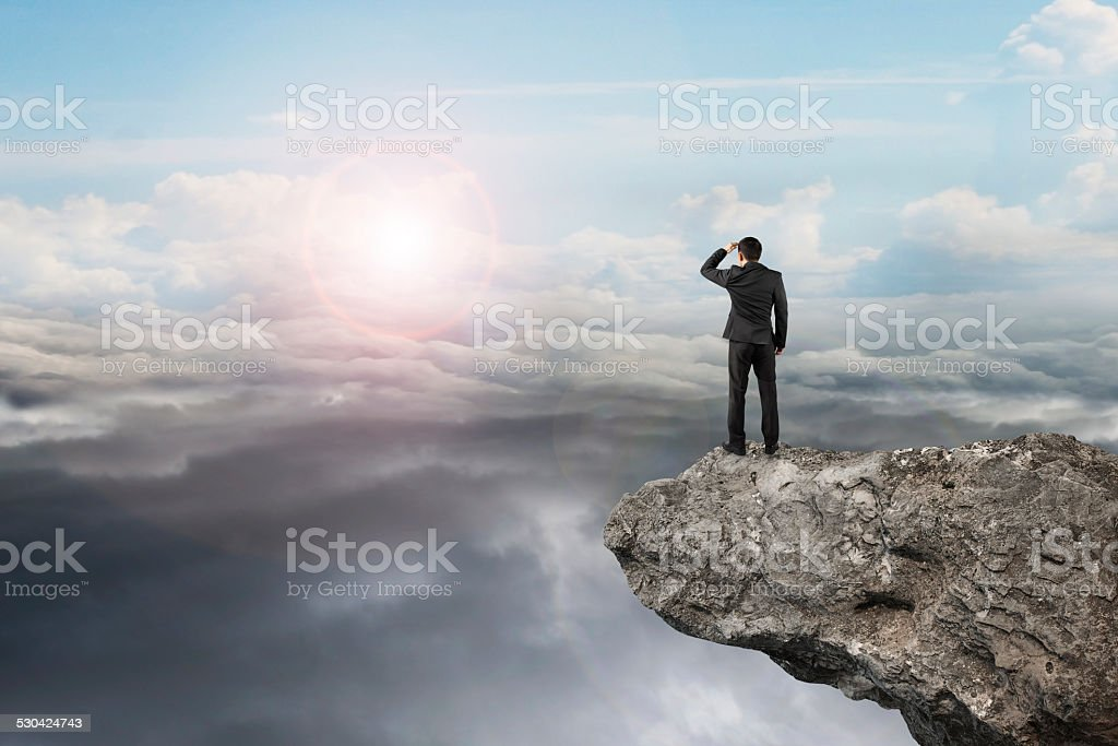businessman looking on cliff with natural sky daylight cloudscap stock photo