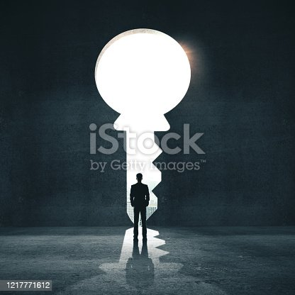 Businessman in concrete room looking on door in form key with light. Motivation and startup concept.