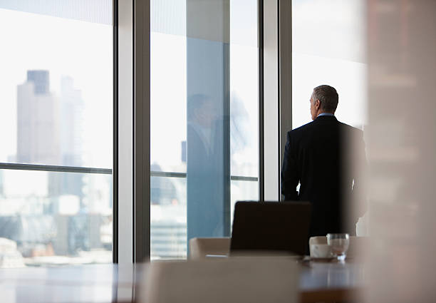 businessman looking out conference room window - looking at view stock pictures, royalty-free photos & images