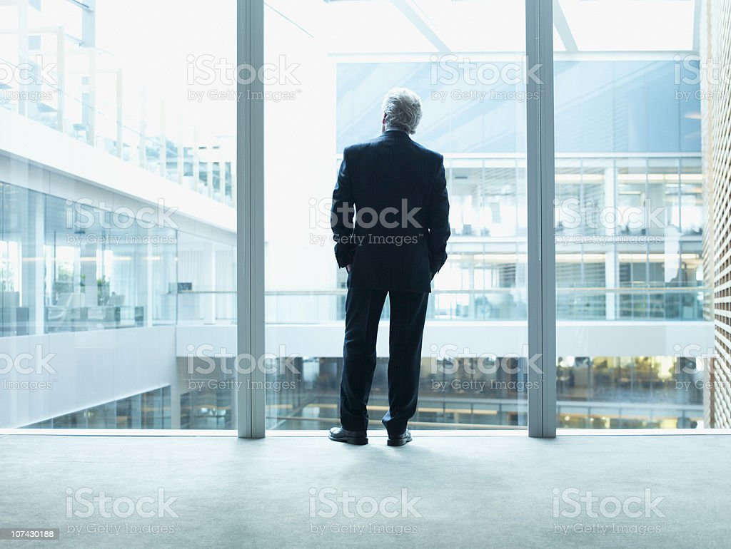 Businessman looking out glass wall in office stock photo