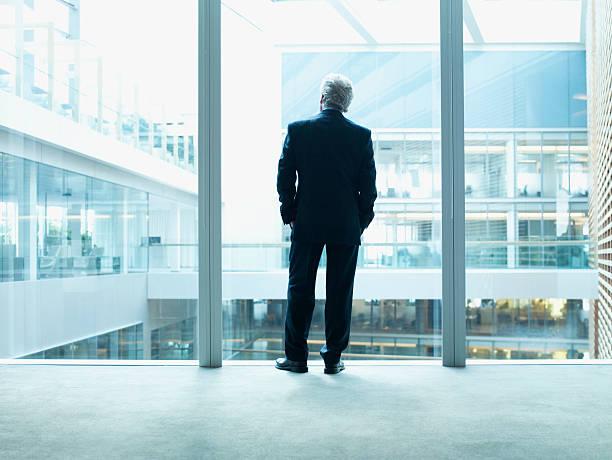 empresário, olhando para a parede de vidro do escritório - old men window imagens e fotografias de stock