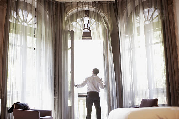 Businessman looking out hotel room window stock photo