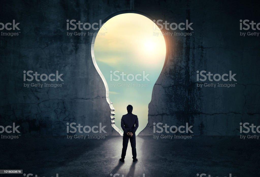 Geschäftsmann aus abstrakten Öffnung in Wand mit hellem Tageslicht in konkrete Interieur. Konzept für den Erfolg. - Lizenzfrei Abstrakt Stock-Foto