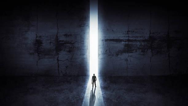 Geschäftsmann aus abstrakter Öffnung in Wand mit hellem Tageslicht im Betoninneren. Erfolgskonzept – Foto