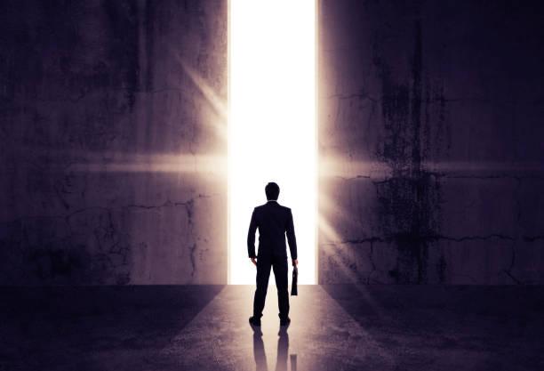 Geschäftsmann aus abstrakten Öffnung in Wand mit hellem Tageslicht in konkrete Interieur. Konzept für den Erfolg. – Foto