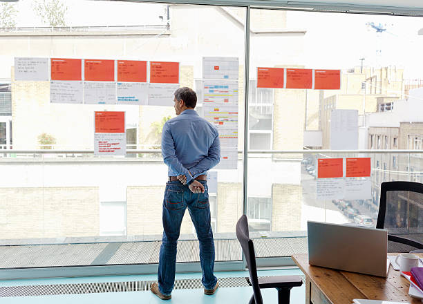 businessman looking out office window - projektledning bildbanksfoton och bilder