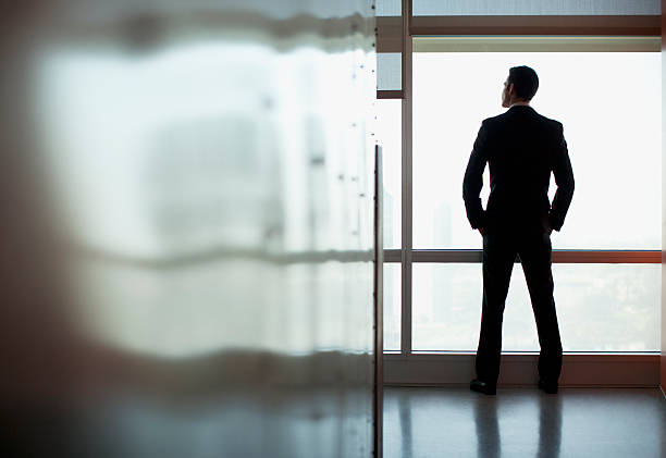 Businessman looking out office window stock photo
