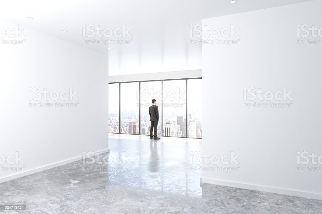 Businessman looking out the window in empty office with concrete stock photo