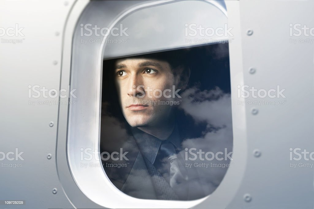 Businessman Looking Out Window of Airplane stock photo