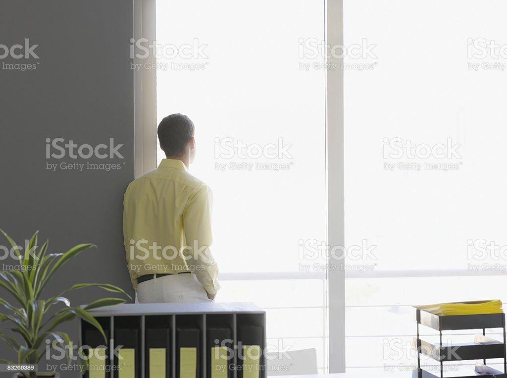 Uomo d'affari guardando fuori la finestra foto stock royalty-free