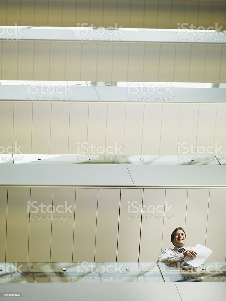 Businessman looking over balcony in atrium royalty-free stock photo