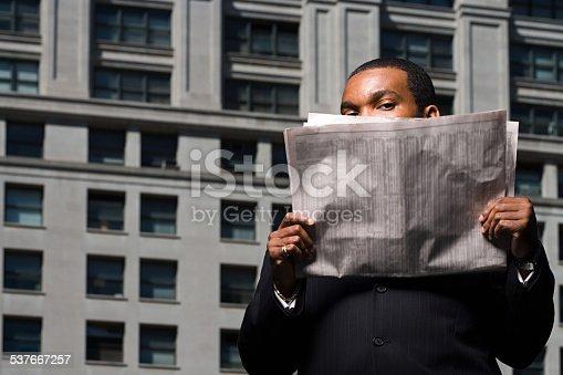 istock Businessman looking over newspaper 537667257