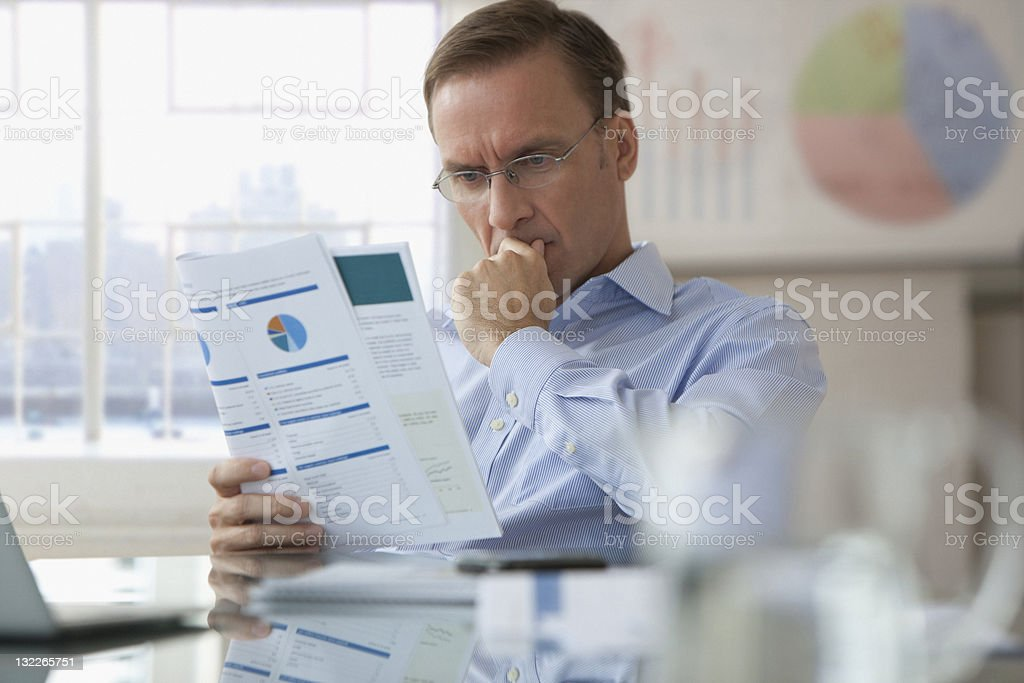 Businessman looking over report stock photo