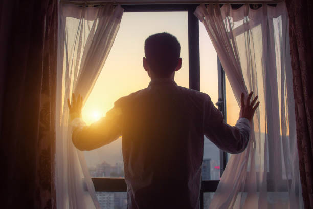 Businessman looking sunrise standing by window stock photo