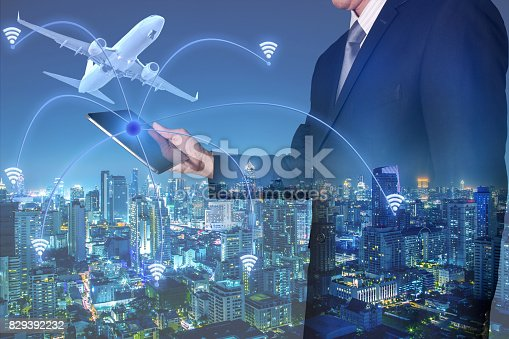 istock businessman looking the tablet, airplane, smart city and wireless network 829392232